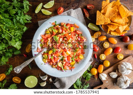 Tex Mex Pico de Gallo with nacho tortilla chips. The bowl of tomato salsa is seen from above, flat lay, and on the table typical ingredients such as scattered tomatoes, lime and cilantro and garlic. Foto stock ©