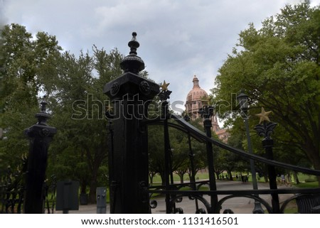 Stock Photo Texas Capitol in Austin with wrought iron fence with stars in foreground.