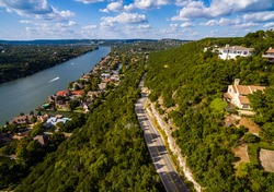 Texas Hill Country,  Mount Bonnell. Road to Texas aerial Shot over Austin , Texas. Windy road and Houses along the Colorado River or Town Lake with boats driving across the water in Austin , Texas