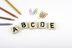 Text: abcde from wooden letterson on white office desk