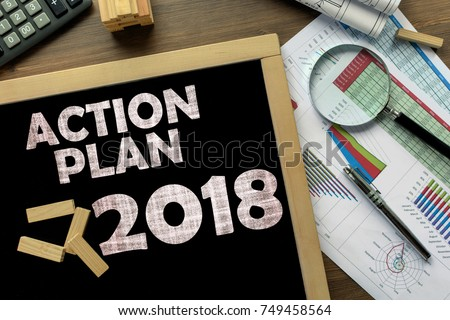 Text Action Plan 2018 on the blackboard on the desk with office business accessories