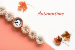 Text Autumntime, alarm clock and decorative white pumpkins. Layered off white and orange paper flat lay with dry maple leaves. Creative seasonal arrangement, monochromatic look.