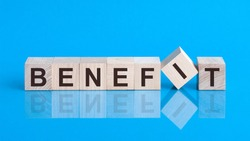 Text benefit on wood cube block, stock investment concept. The text benefit is written on the cubes in black letters, the cubes are located on a blue glass surface