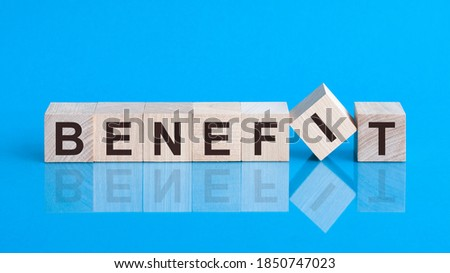 Text benefit on wood cube block, stock investment concept. The text benefit is written on the cubes in black letters, the cubes are located on a blue glass surface Сток-фото ©
