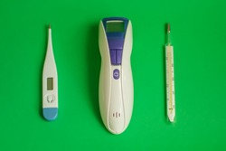 Text BEST Thermometer for home. Three different types of thermometers on green background. mercury, infrared contactless Thermometer. Soft focus