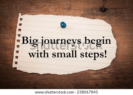 Text big journeys begin with small steps on note paper