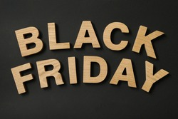 Text Black Friday made of wooden letters on black background