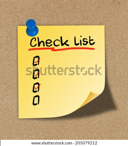 Text check list on yellow note pinned on cork board.