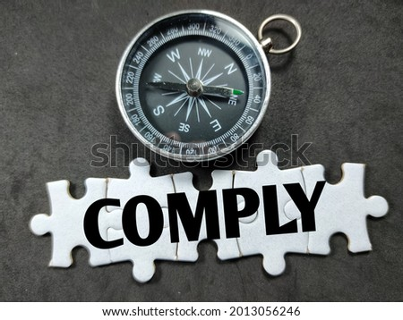Text COMPLY on jigsaw puzzle with compass on a black background. Stock photo ©