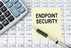 text Endpoint Security on yellow paper next to financial reports, calculator and gold pen