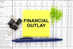Text Financial Outlay on financial tables with pen and paper clips. Business and financial conzept