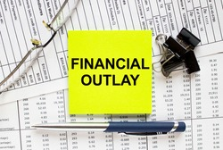 Text Financial Outlay on financial tables with pen, glasses and paper clips. Business and financial conzept