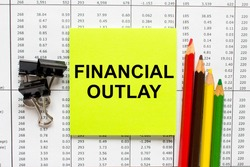 Text Financial Outlay on financial tables with pencils, glasses and paper clips. Business and financial conzept