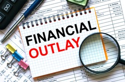 Text Financial Outlay on notepad with calculator, clips, pen on financial report. Business and financial conzept