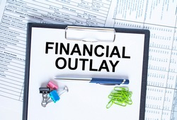 Text Financial Outlay on the folder that is located on the financial reports with calculator and stationery clips. Business and financial concept