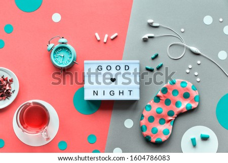 """Text """"Good night"""" on trendy lightbox. Pink sleeping mask with polka dots, alarm clock, earphones and earplugs. Pills, capsules and calming tea. Flat lay, two tone orange coral and silver background."""