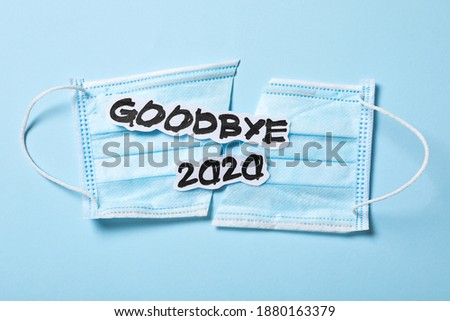 Text Goodbye 2020 and medical face mask on light blue background, flat lay