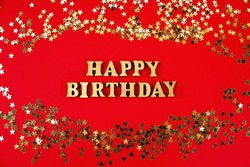 Text Happy birthday laid out of gold letters on a beautiful background. Golden stars confetti.