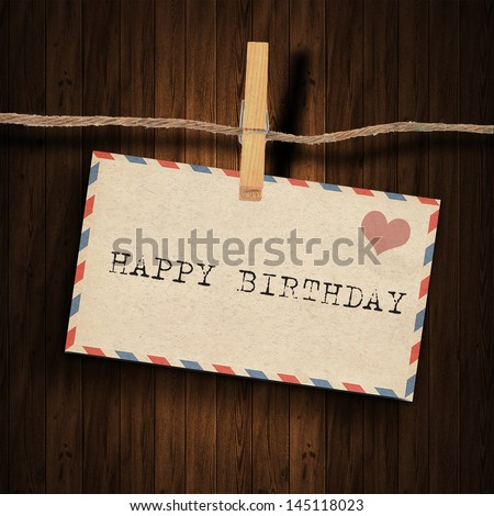 text happy birthday  on the old envelope and clothes peg wood background