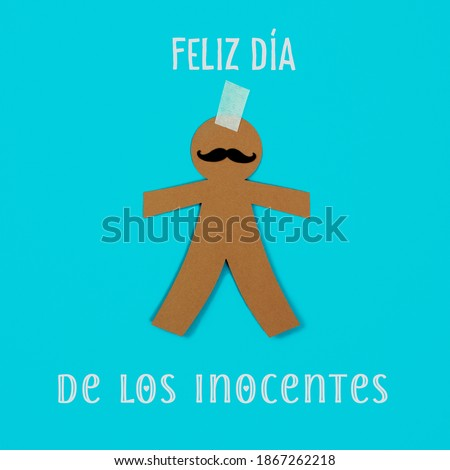 text happy innocents day written in spanish and a paper man, as a prank for the dia de los inocentes, the innocents day, a feast held in spain and hispanic america equivalent to april fools day Foto stock ©