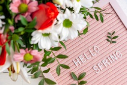 Text Hello Spring on pink letter board and bouquet of colored flowers. Concept Springtime mood and happiness