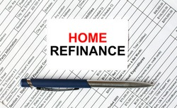 Text Home Refinance written on a business card lying on financial tables with a blue metal pen. Business and financial concept