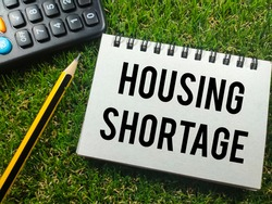 Text HOUSING SHORTAGE with pencil and calculator on grass background.