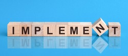 Text IMPLEMENT on wood cube block, stock investment concept. The text IMPLEMENT is written on the cubes in black letters, the cubes are located on a blue glass surface.