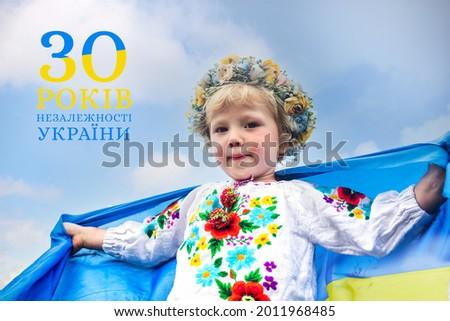 Text in ukrainian Independence Day of Ukraine 30 years. Ukrainian flag blue and yellow flag of Ukraine in hands of happy girl Ukrainian. Сток-фото ©