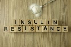 Text insulin resistance from wooden blocks with spoon of sugar, diabetic concept