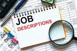 Text Job Descriptions on notepad with calculator, clips, pen on financial report