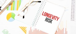 Text LONGEVITY RISK on white notepad, glasses, graphs and diagrams.