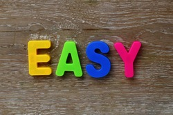 Text made in multicolored magnetic letters. EASY. Scratched wooden grunge background.