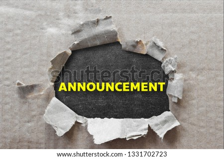Text message ANNOUNCEMENT on brown torn paper with black backdrop.