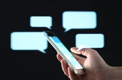 Text messages in cellphone screen with abstract hologram speech bubbles. Instant messaging app. Texting, group chat, sexting or sms concept. Customer service help desk with live support chatbot.