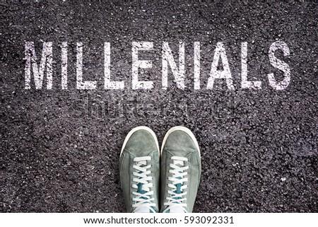 Text Millenials written on asphalt with shoes