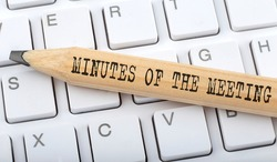 Text MINUTES OF THE MEETING on wooden pencil on white keyboard. Business