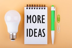 Text MORE IDEAS on a white piece of paper in notebook next to a light bulb and a green pen. Imagination concept.