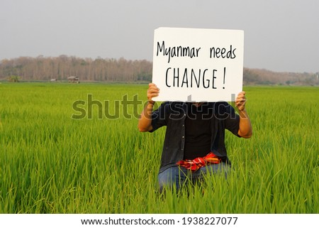 Text ' Myanmar needs CHANGE' on sign board hold by man at greed paddy field. Concept protesting for democracy and against the coup in Myanmar. Photo stock ©