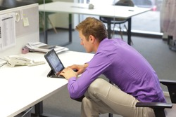 text neck - man in slouching position on office chair working with tablet at desk
