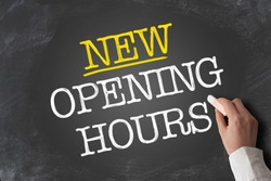 text NEW OPENING HOURS written on blackboard with hand holding piece of chalk