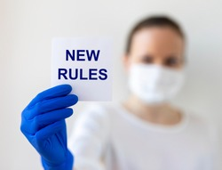 Text New Rules written on note paper in a hand in protective glove with blurring doctor in mask on a white background. Pandemic and rules concept.