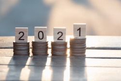 Text of 2021 number written on wooden blocks on top of coins stacks  with nature sunset background, Business and Saving money for new life new year concept, Selective focus.
