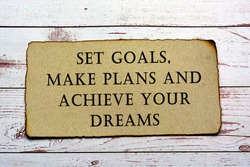 Text on brown paper with burnt edge - Set goals, make plans, achieve your dreams