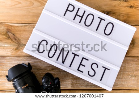 """Text """"photo contest""""  written on white slate with camera on wooden background. Suitable for advertising"""