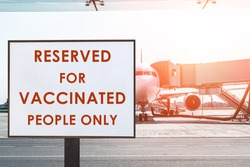 Text plate RESERVED FOR VACCINATED PEOPLE ONLY at boarding gate in airport terminal against big commercial plane on airfield at sunrise or sunset. Travel and tourist destination at new normal concept