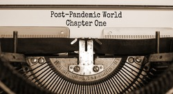Text 'post-pandemic world chapter one' typed on retro typewriter. Business and post-pandemic covid-19 concept. Sepia effect.