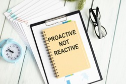 Text Proactive not reactive on white paper book on table, business concept
