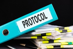Text PROTOCOL is written on a folder lying on a stack of papers with a pen on the table. Business concept