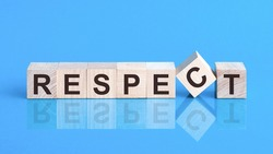 Text Respect on wood cube block, stock concept. The text respect is written on the cubes in black letters, the cubes are located on a blue glass surface.